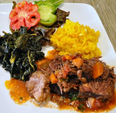 Beef Braised in Barolo Wine served with rice nd colorful vegetables on a white plate