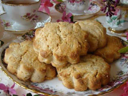 pile of honey ginger scones on a plate with a floral tablecloth in the background