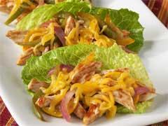 3 chicken fajita lettuce wraps lined up on a white plate