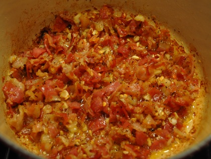 A pan of sizzling tomatoes boiling down to make the sauce.