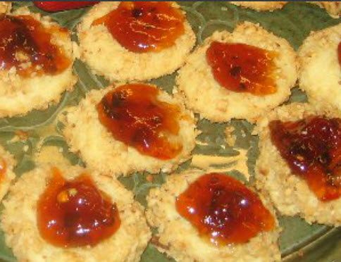 Plate of savory Cheddar Cheese Thumbprint Cookies topped with pepper jelly